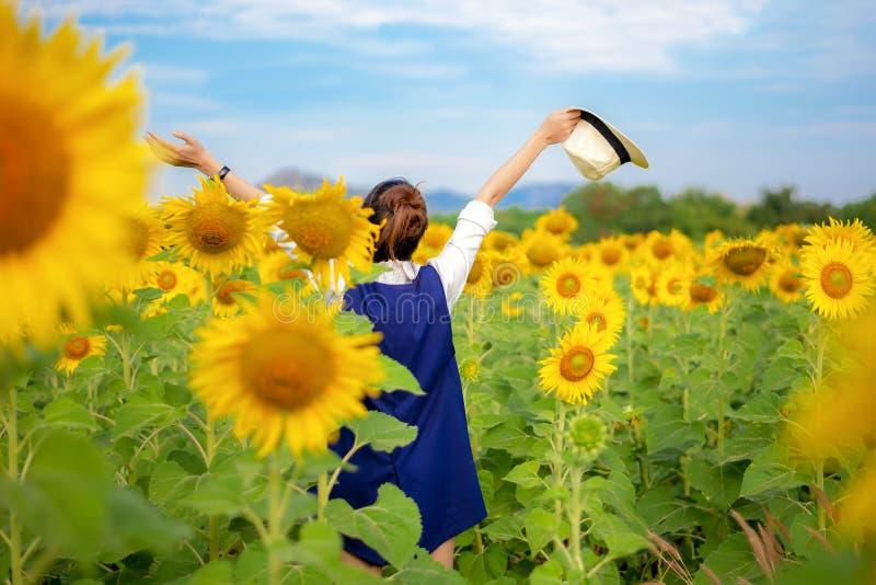 Achtermening van de vrouwen van de reislevensstijl met handen op hoed op zonnebloemgebied, in de zomerdag en gelukkige roepingen stock foto