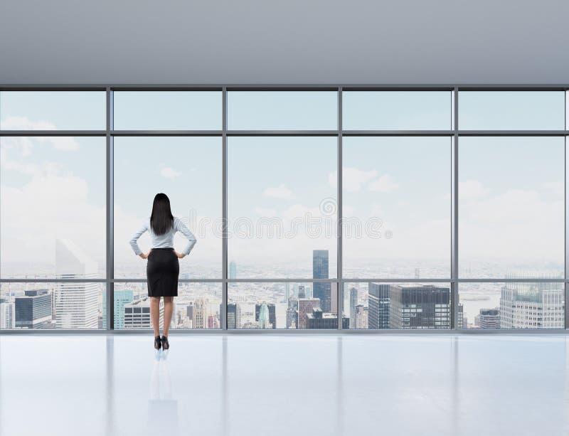 Achtermening van donkerbruine vrouw in het bureau dat door het venster kijkt royalty-vrije stock afbeeldingen