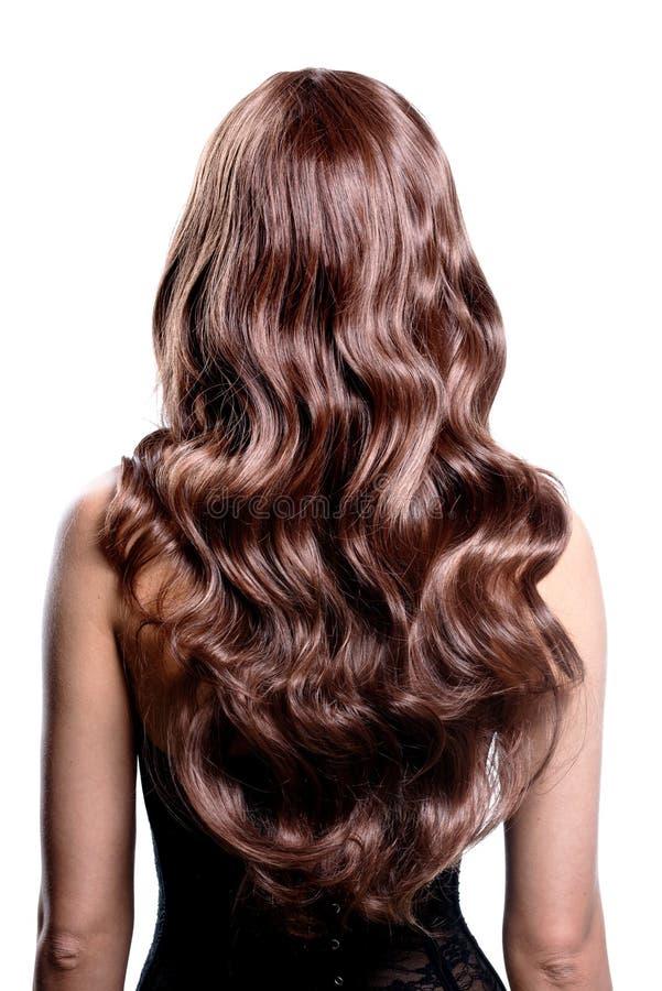 Achtermening van donkerbruine vrouw met lang zwart krullend haar