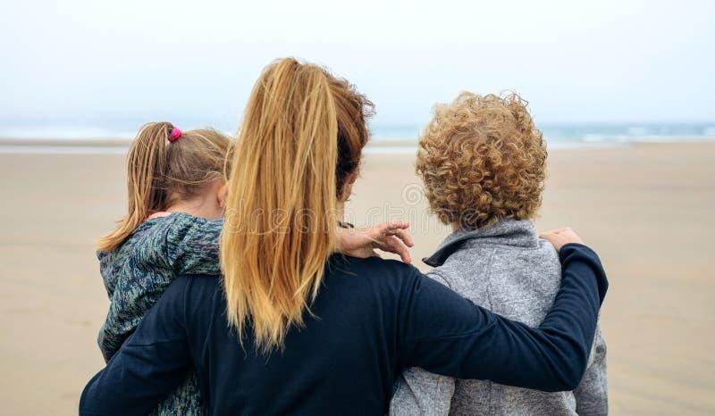Achtermening van drie generatieswijfje die op zee kijken royalty-vrije stock afbeelding