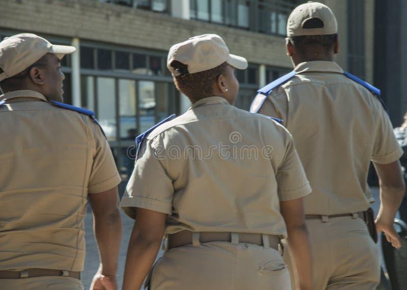 Achtermening van drie Zuidafrikaanse verkeersambtenaren, één wijfje en twee mannetjes, die kappen dragen royalty-vrije stock afbeelding