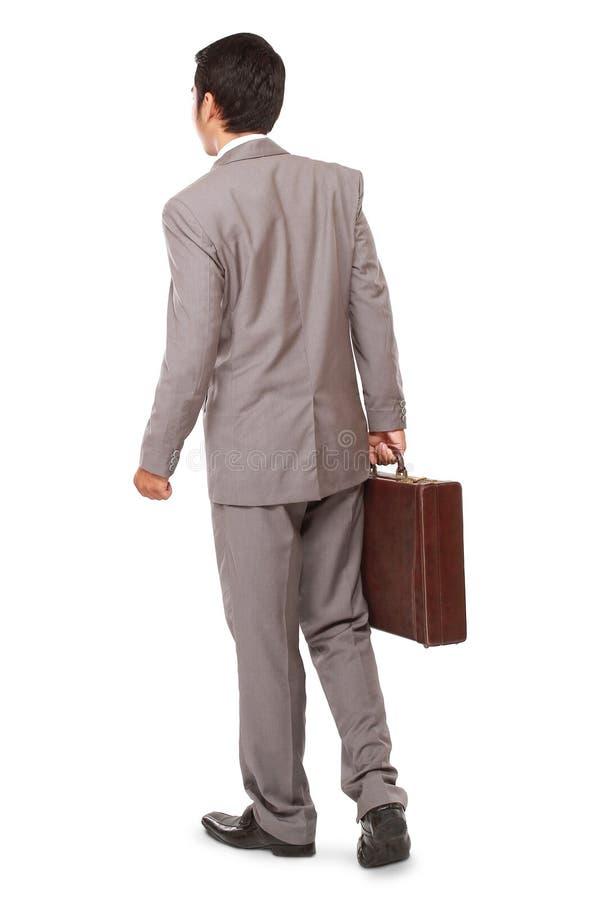 Achtermening van een bedrijfsmens die en een aktentas bevinden zich houden stock afbeelding