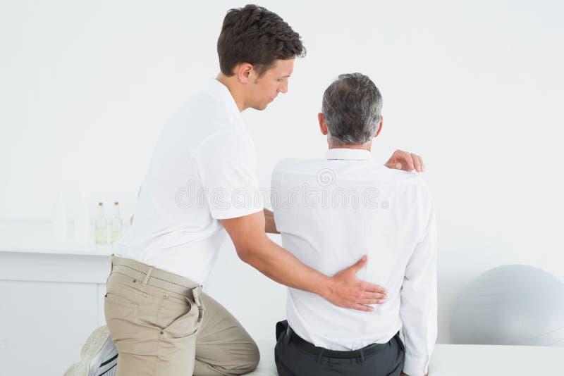 Achtermening van een chiropracticus die de mens onderzoeken stock fotografie