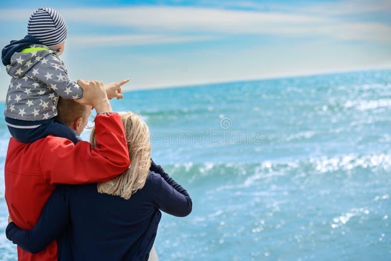 Achtermening van een gelukkige familie bij tropisch strand op de zomervakantie royalty-vrije stock foto's