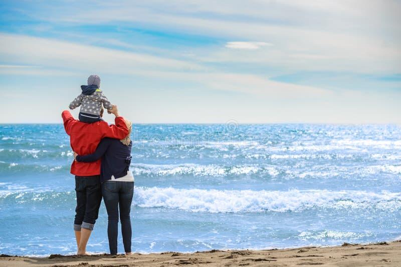Achtermening van een gelukkige familie bij tropisch strand op de zomervakantie stock fotografie
