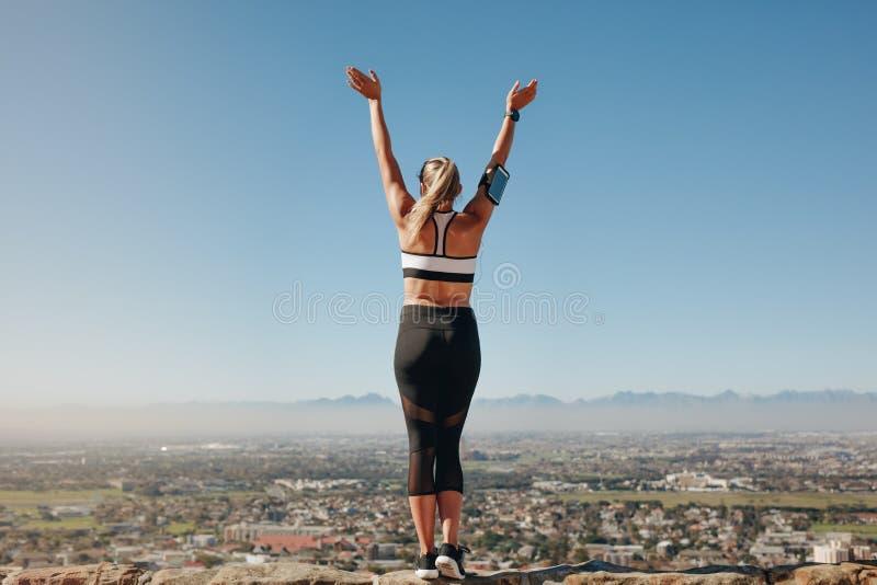 Achtermening van een geschiktheidsvrouw die zich op een heuvel bevinden royalty-vrije stock foto's