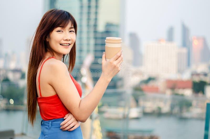 Achtermening van een glimlachende jonge vrouw die zich bij de horizon van Bangkok met een kop van koffie na het werken in de avon royalty-vrije stock fotografie