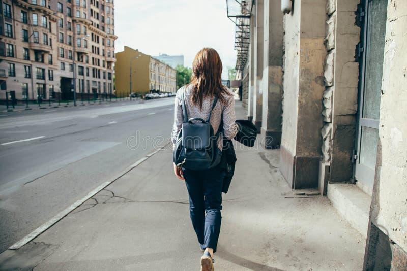 Achtermening van een hipstermeisje die op stadsstraat lopen royalty-vrije stock afbeeldingen