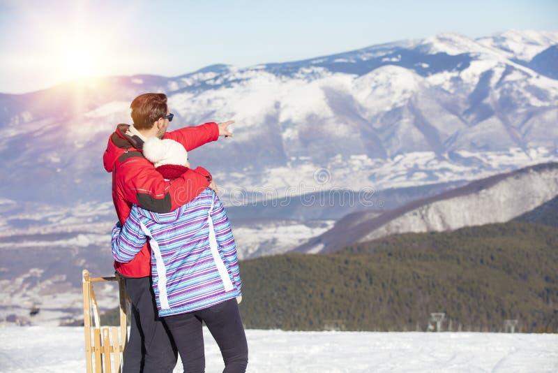 Achtermening van een houdend van paar die in de jasjes van de bontkap gesneeuwde bergketen bekijken royalty-vrije stock foto