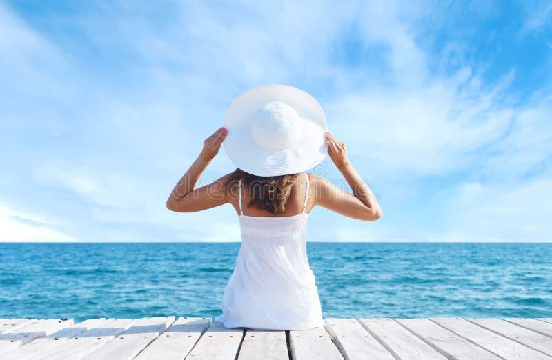 Achtermening van een jong meisje die zich op een pijler bevinden Overzeese en Hemelachtergrond Vakantie en reizend concept royalty-vrije stock foto's