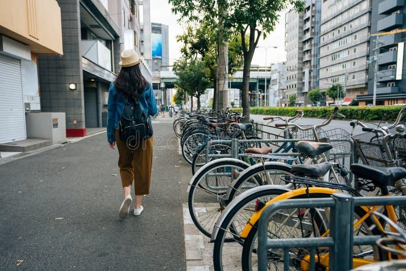 Achtermening van een jong wijfje die backpacker door het fietsenparkeerterrein lopen in de stad de Aziatische reiziger met stroho royalty-vrije stock afbeeldingen