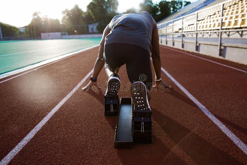 Achtermening van een jonge mannelijke atleet bij startblok royalty-vrije stock foto's