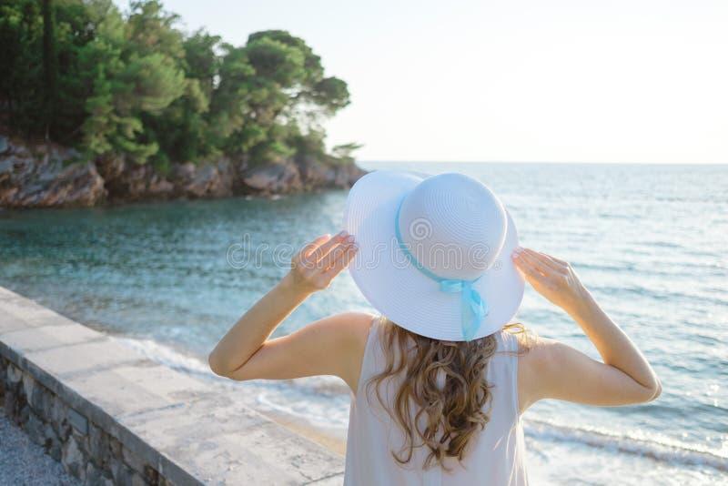 Achtermening van een jonge mooie vrouw die haar strohoed houden bij het strand en aan de overzeese horizon kijken stock foto