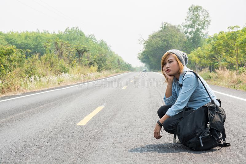 Achtermening van een jonge vrouw lift het dragen rugzakzitting stock foto's