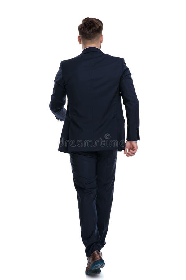 Achtermening van een lopende zakenman stock afbeeldingen