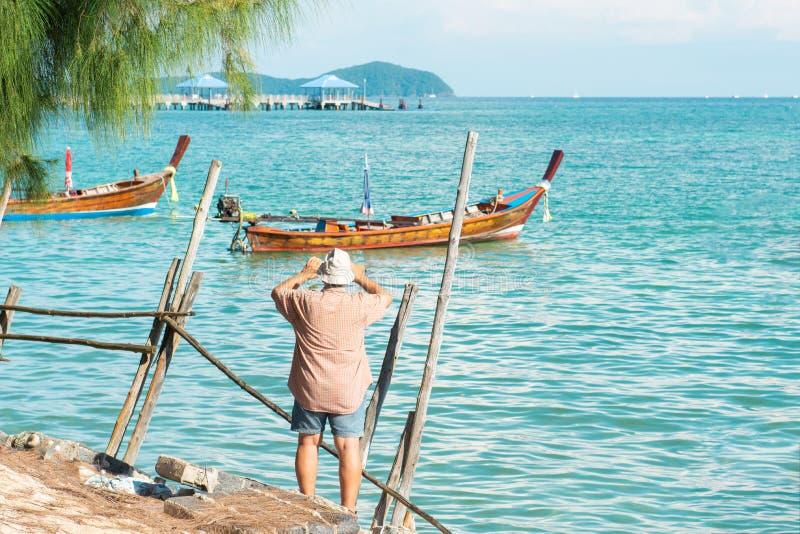 Achtermening van een medio oude mensentoerist in toevallige kleding die foto van lokale lange staartboot nemen met smartphone voo royalty-vrije stock afbeelding