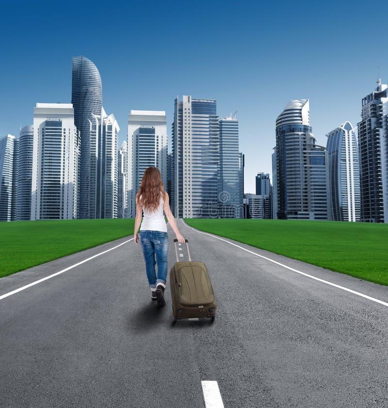 Achtermening van een meisje met een koffer die de stad ingaan royalty-vrije stock fotografie