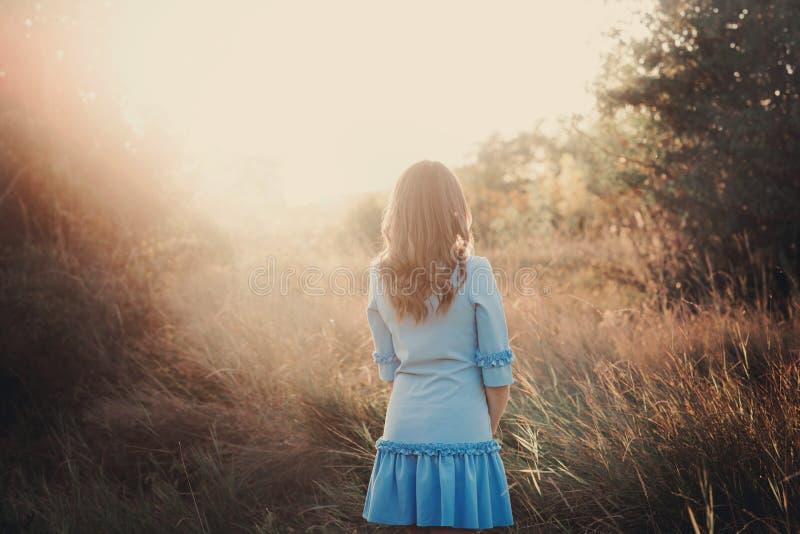 Achtermening van een mooi jong vrouw of meisje die op zeer groene weide op de zonsondergang een letten stock afbeeldingen