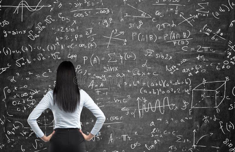 Achtermening van een nadenkende vrouw die probeert om wiskundeproblemen op te lossen stock fotografie