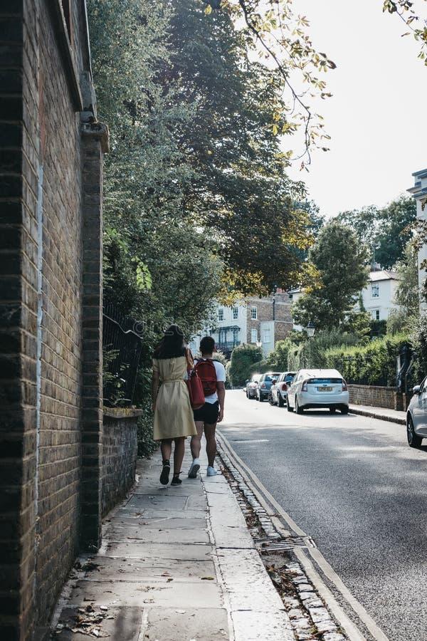 Achtermening van een paar die op een straat in Hampstead, Londen lopen, royalty-vrije stock foto's
