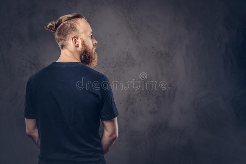 Achtermening van een roodharige gebaarde mens gekleed in een zwarte t-shirt Geïsoleerd op de donkere geweven achtergrond stock foto's