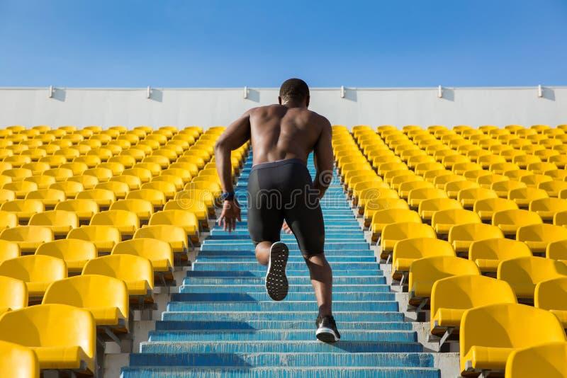 Achtermening van een sportman die snelheidsoefening voor spieren doen stock afbeelding