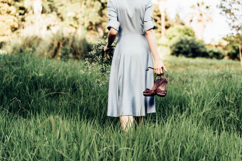 Achtermening van een vrouw in een kleding die langs een weide blootvoets met schoenen in haar hand lopen stock foto's