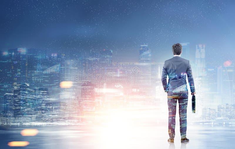 Achtermening van een zakenman die een nachtstad bekijken stock foto