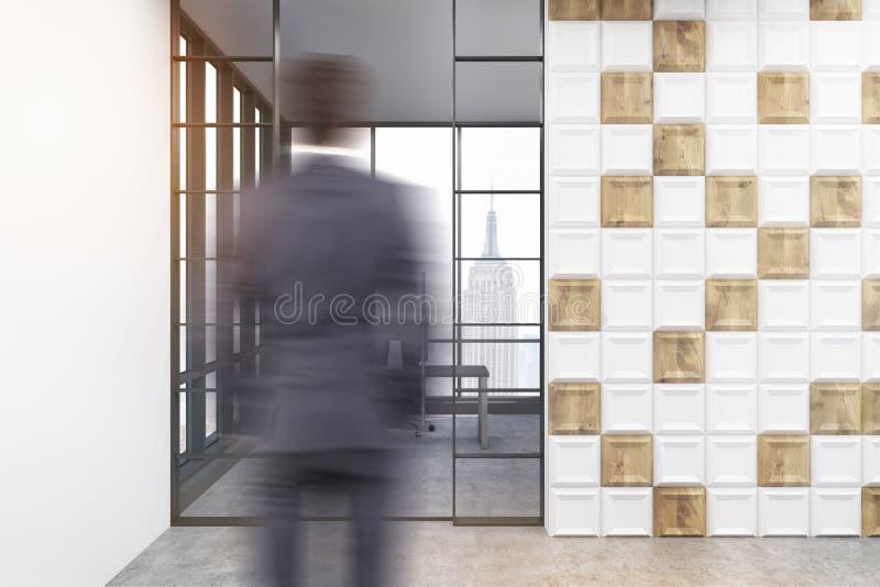 Achtermening van een zakenman die een ruimte met witte en houten tegels op de muur en de panoramische vensters enterting royalty-vrije stock fotografie