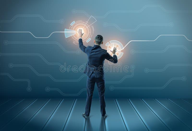 Achtermening van een zakenman wat betreft pictogrammen op het digitale scherm met beide handen stock afbeelding
