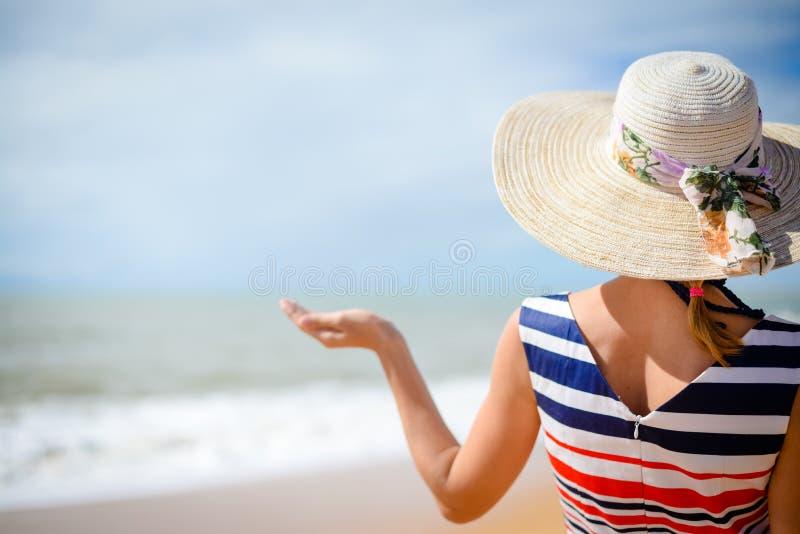 Achtermening van elegante de handpalm van de vrouwenholding omhoog met de zomeroverzees op de achtergrond royalty-vrije stock foto's