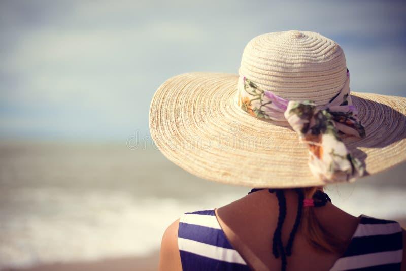 Achtermening van elegante mooie vrouw in kleding en strohoed op het strand stock foto