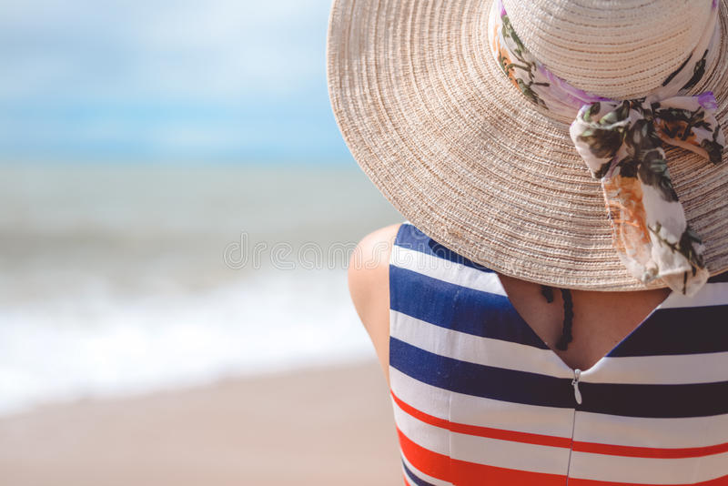 Achtermening van elegante mooie vrouw in kleding en strohoed op het strand royalty-vrije stock foto's