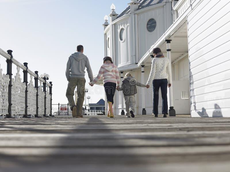 Achtermening van Familie die langs Pijler lopen royalty-vrije stock afbeeldingen