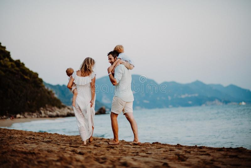 Achtermening van familie met twee peuterkinderen die op strand op de zomervakantie lopen royalty-vrije stock afbeelding