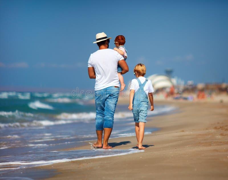 Achtermening van familie, vader met jonge geitjes die op zandig strand dichtbij het overzees lopen, de zomervakantie stock afbeelding