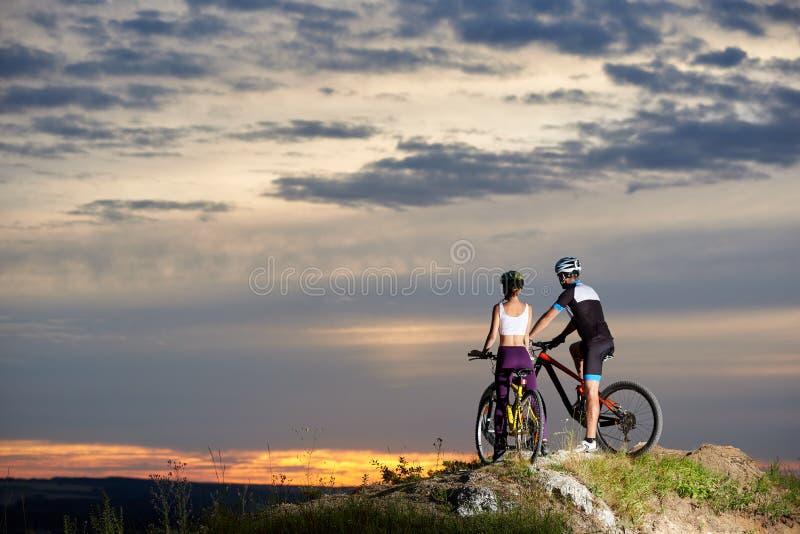 Achtermening van fiets van de paar de berijdende berg op bovenkant die van de zonsondergang genieten royalty-vrije stock foto's