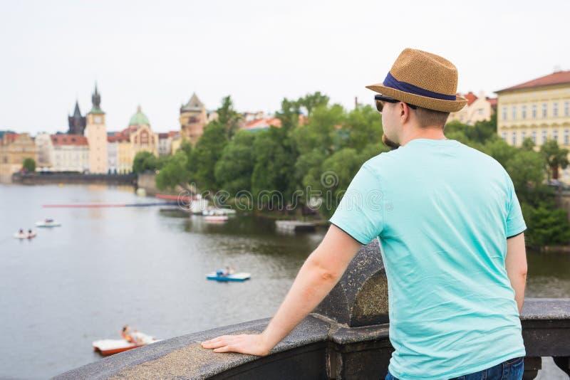 Achtermening van gelukkige modieuze toerist op Charles Bridge, Praag, Tsjechische Republiek Knappe mens die in Europa reizen stock afbeeldingen