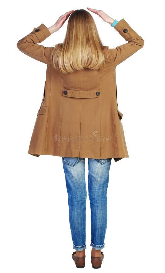 Achtermening van geschokte vrouw in bruine mantel stock afbeelding