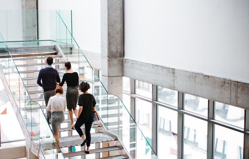 Achtermening van groep jong zakenlui die omhoog de treden lopen stock fotografie
