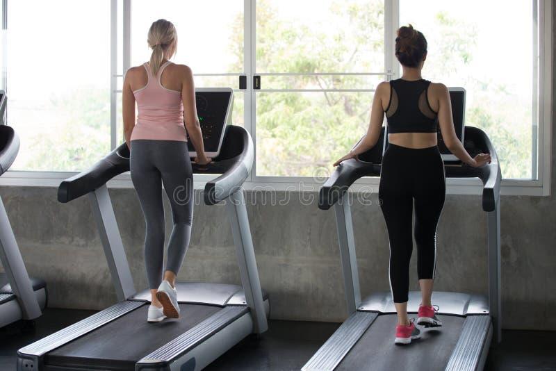 Achtermening van groep jongeren die op tredmolens in sportgymnastiek lopen twee de agent van de geschiktheidsvrouw bij het runnen stock afbeeldingen
