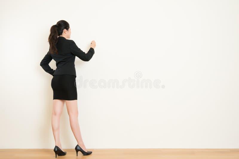 Achtermening van het bedrijfsvrouw schrijven op witte muur stock foto