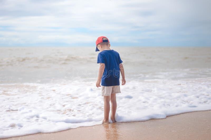 Achtermening van het blootvoetse jongen lopen langs het strand buiten tijdens zonsondergang royalty-vrije stock afbeeldingen