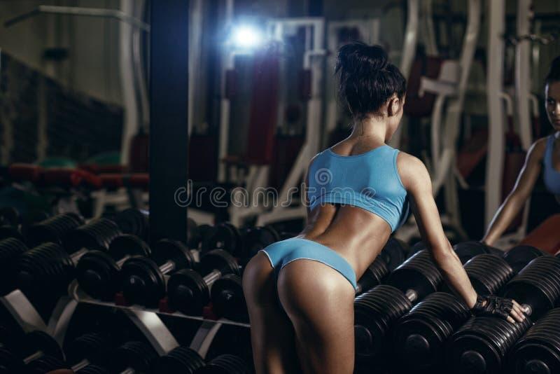 Achtermening van het donkerbruine sexy geschiktheidsmeisje stellen in gymnastiek royalty-vrije stock afbeelding