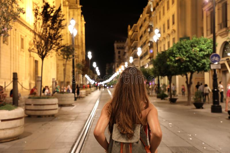 Achtermening van het jonge toeristenvrouw lopen in de straat van Sevilla in Th stock afbeelding