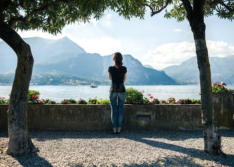 Achtermening van het jonge vrouw ontspannen op kade van bergmeer Como royalty-vrije stock afbeelding