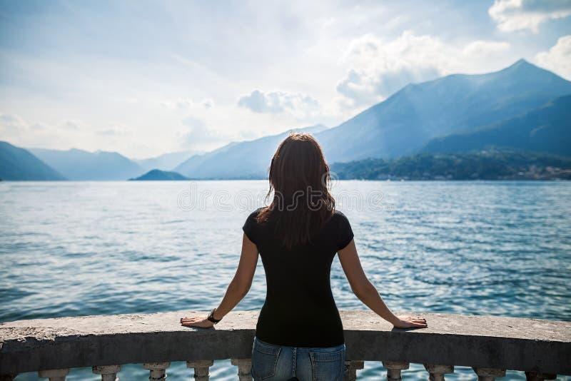 Achtermening van het jonge vrouw ontspannen op terras op meer Como, Italië stock afbeeldingen