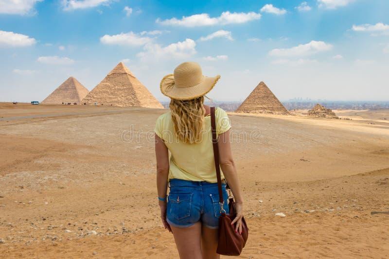 Achtermening van het jonge wijfje die op de Grote Piramides van Giza in Egypte letten stock foto