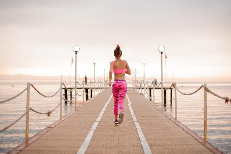 Achtermening van het mooie slanke en jonge meisje lopen over de houten brug royalty-vrije stock foto