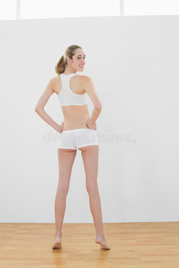 Achtermening van het mooie slanke vrouw stellen in sporthal royalty-vrije stock foto